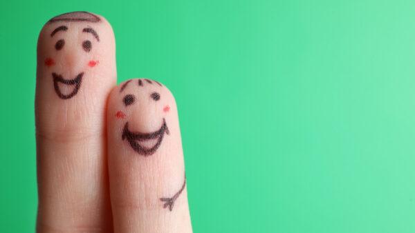 due dita con una faccina sorridente su sfondo verde